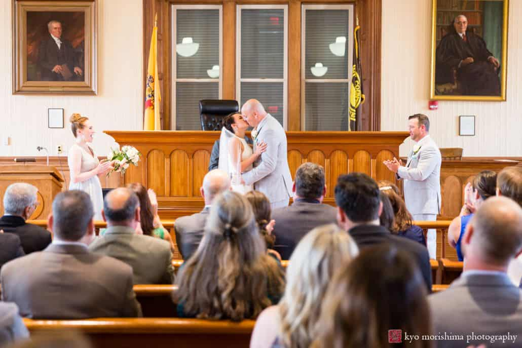 Bride and groom have their first kiss during wedding ceremony as guests applaud at Hunterdon County courthouse, New Hope, PA, BHLDN bridal gown, Men's Warehouse suit, intimate Pennsylvania wedding photographer.