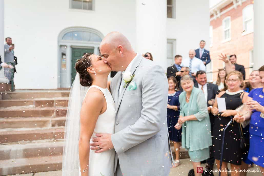 Bride and groom kiss on steps outside Hunterdon County courthouse as guests throw confetti, BHLDN wedding dress, men's warehouse suit, intimate Summer New Hope, PA wedding photographer.