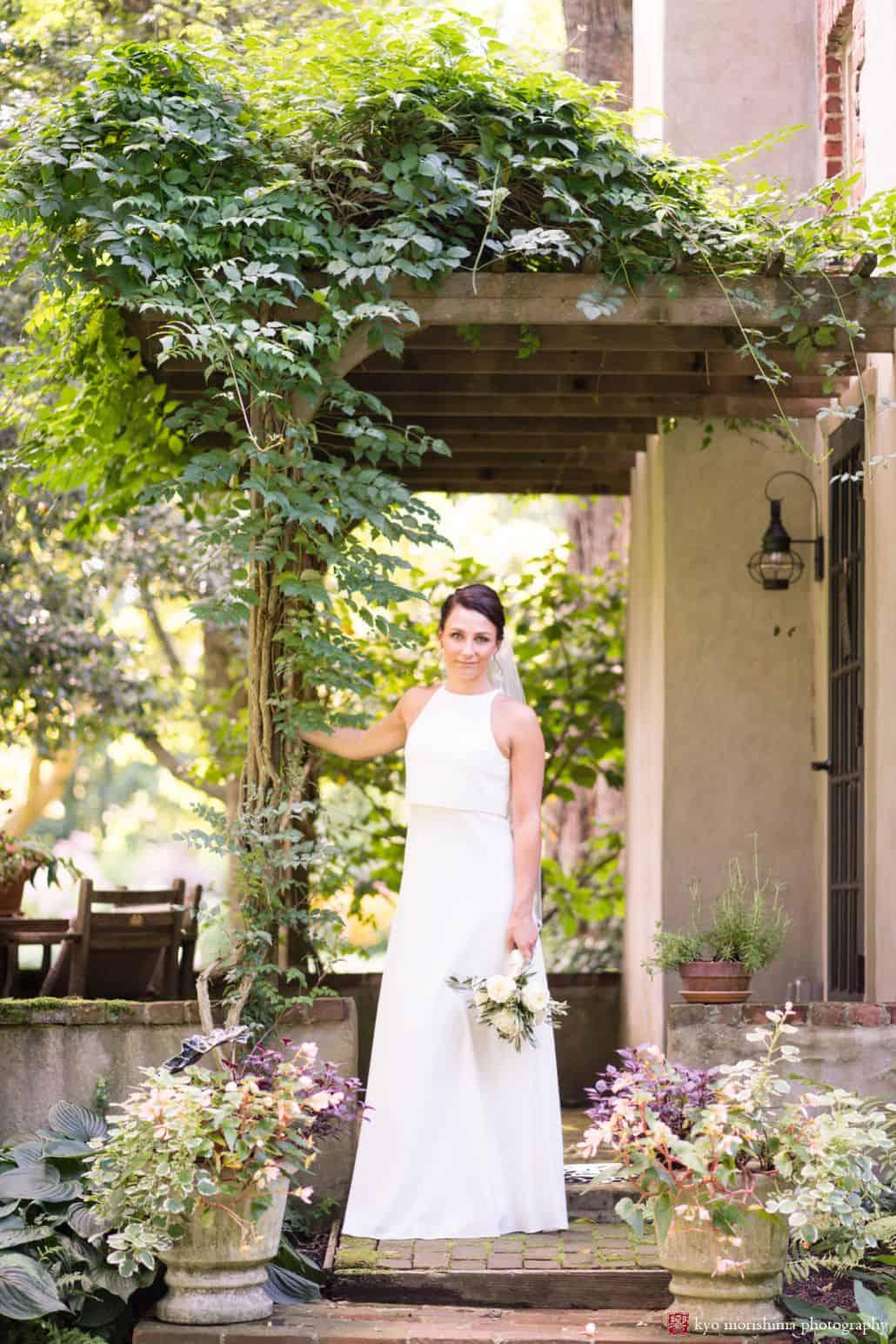 Portrait of bride under vine covered pergola holding white rose bouquet, BHLDN wedding dress, The Pod Shop Flowers, August New Hope, PA wedding photographer.