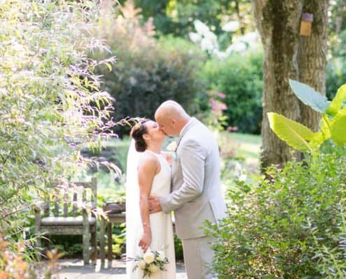 Bride and groom kiss in garden in New Hope, PA, The Pod Shop Flowers rose bouquet, Summer wedding photographer, intimate wedding.