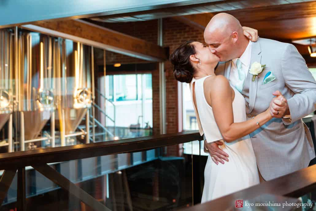 Bride and broom kiss outside bright tanks at Triumph Brewing, BHLDN wedding gown, Men's Warehouse suit, white rose boutineer, The Pod Shope Flowers, New Hope, PA wedding photographer, triumph brewery wedding photos.