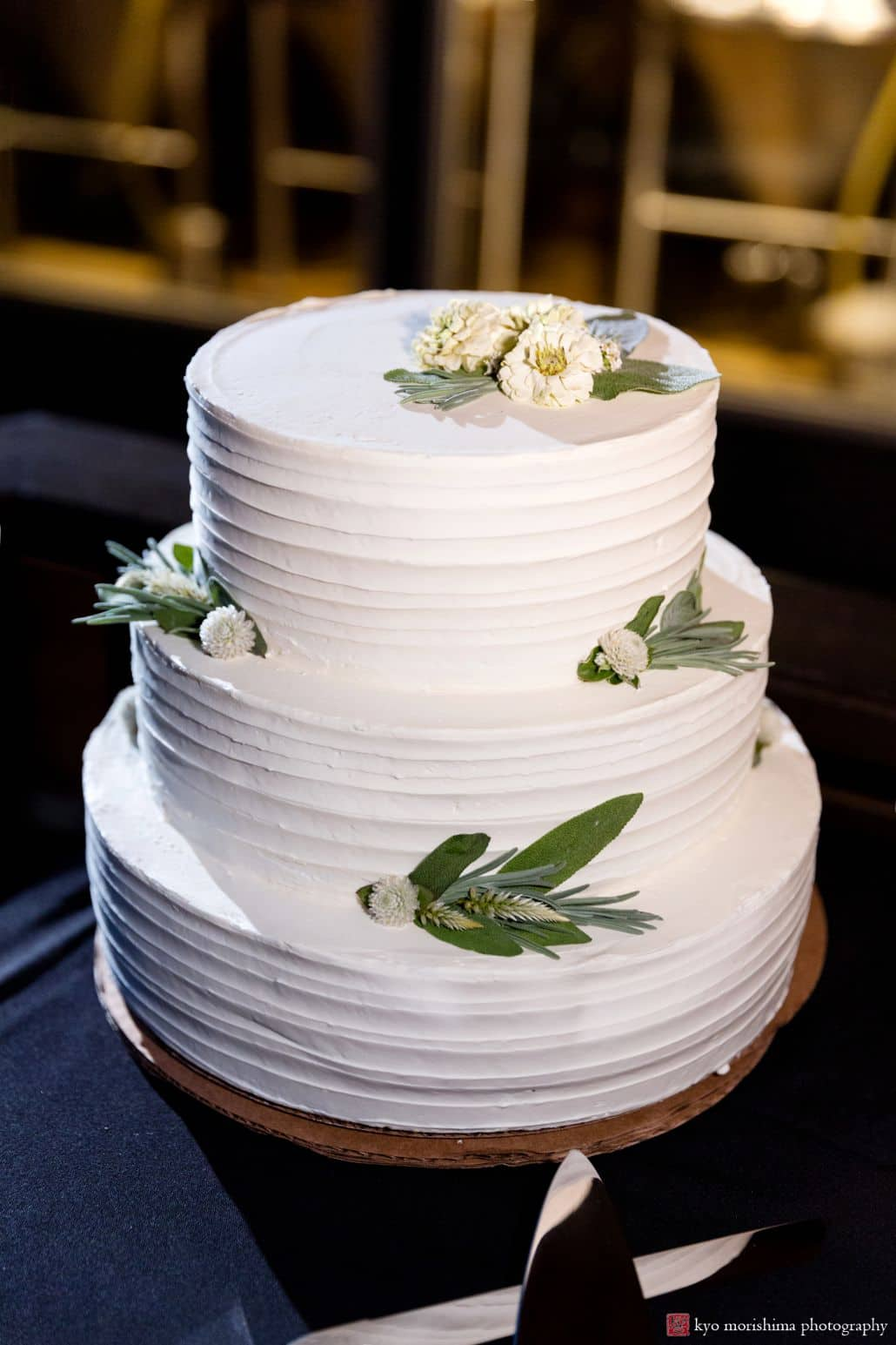 Simple and elegant 3 tier wedding cake with small white flowers and sage leaves, Factory Girl Bake Shop, Triumph Brewing Company, New Hope, PA wedding photographer.
