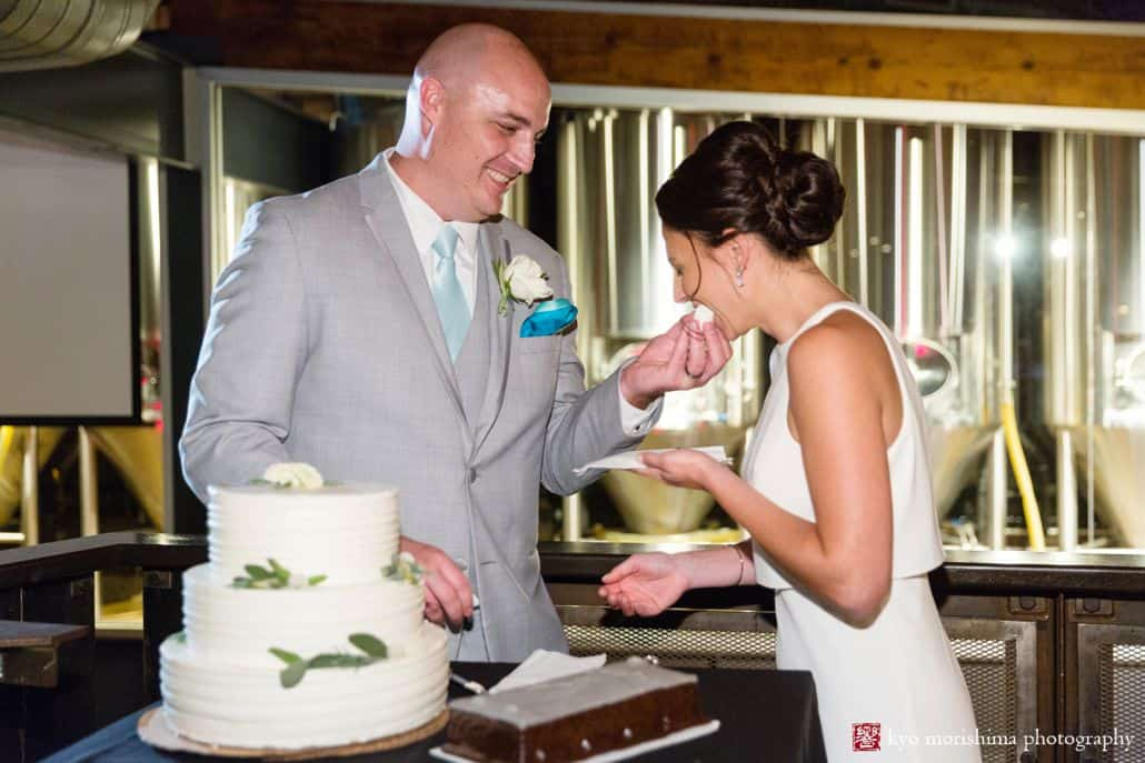 Groom feeds bride cake at Triumph Brewing Co, New Hope, PA, chocolate rectangular groom's cake, Factory Girl Bake Shop, BHLDN wedding dress, Men's Warehouse suit, teal tie and pocket square, intimate wedding photographer, triumph brewery wedding photos.