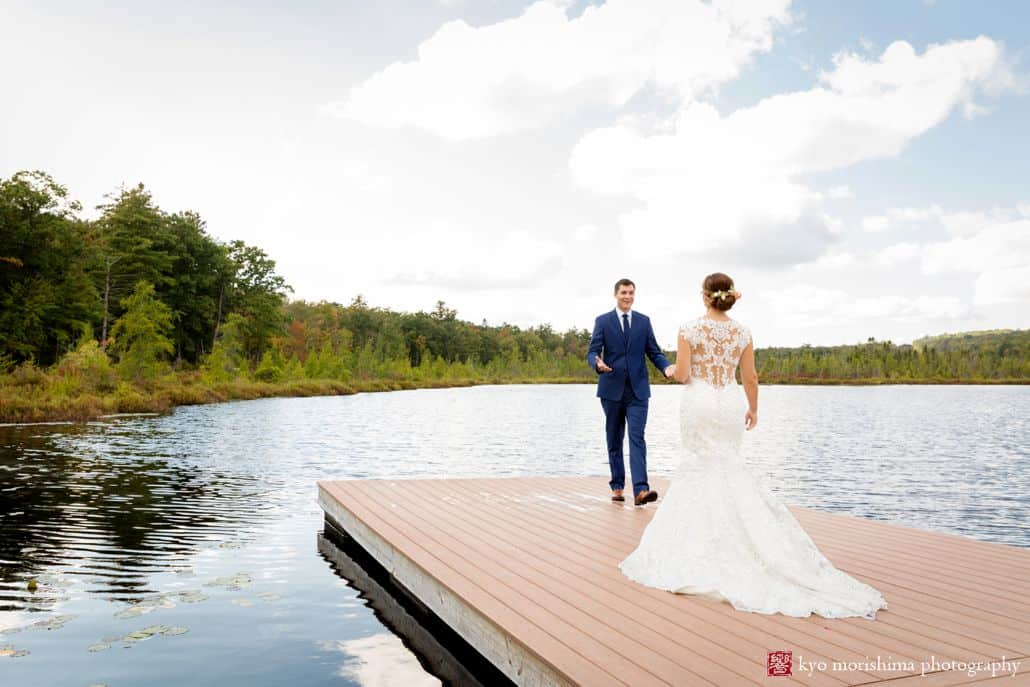Bride and groom stand at end of dock overlooking a pond and treeline at Woodloch Pines in the Poconos, Castle Couture wedding gown, lace back wedding dress, navy groom's suit, outdoor wedding photographer, resort wedding.