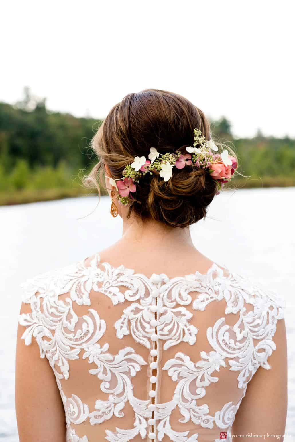 Bride overlooking pond wearing lace back wedding dress by Castle Couture with cloth covered buttons, pink and white flowers in bride's hair with pink rose and eucalyptus seeds, Woodloch Pines wedding photographer, outdoor wedding photography.