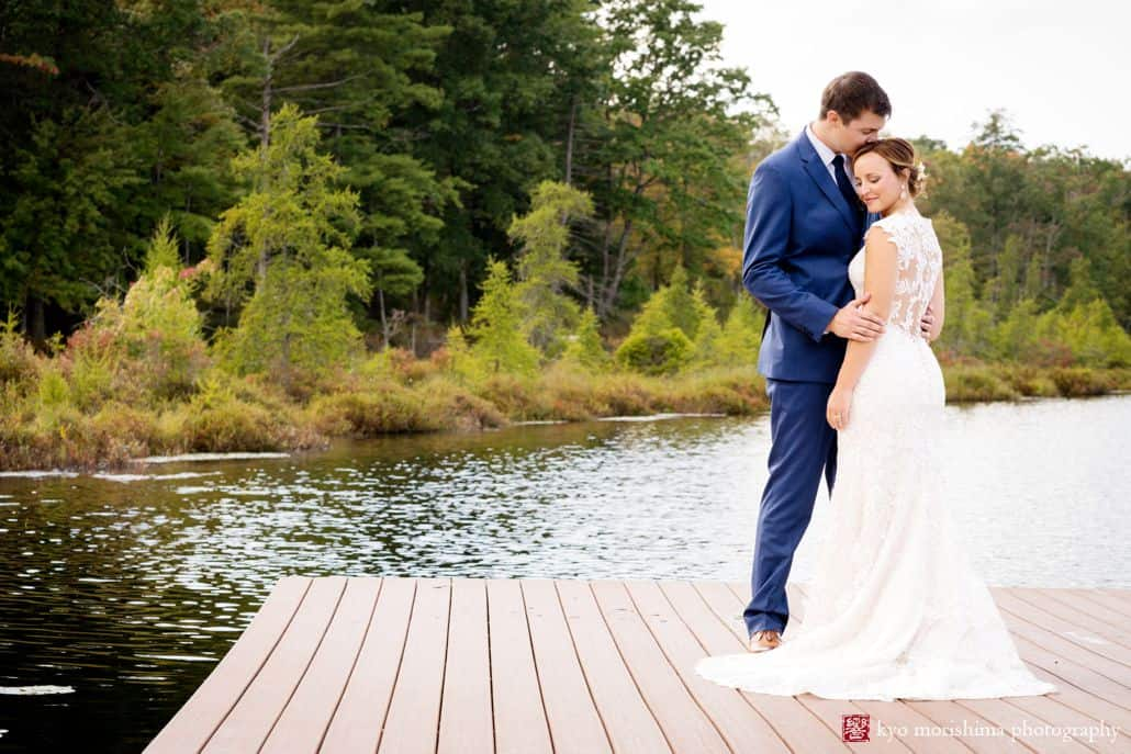 Groom in navy suit kisses bride's head at end of dock overlooking pond and forest at Woodloch Pines resort, Castle Couture wedding gown, outdoor poconos wedding photographer.