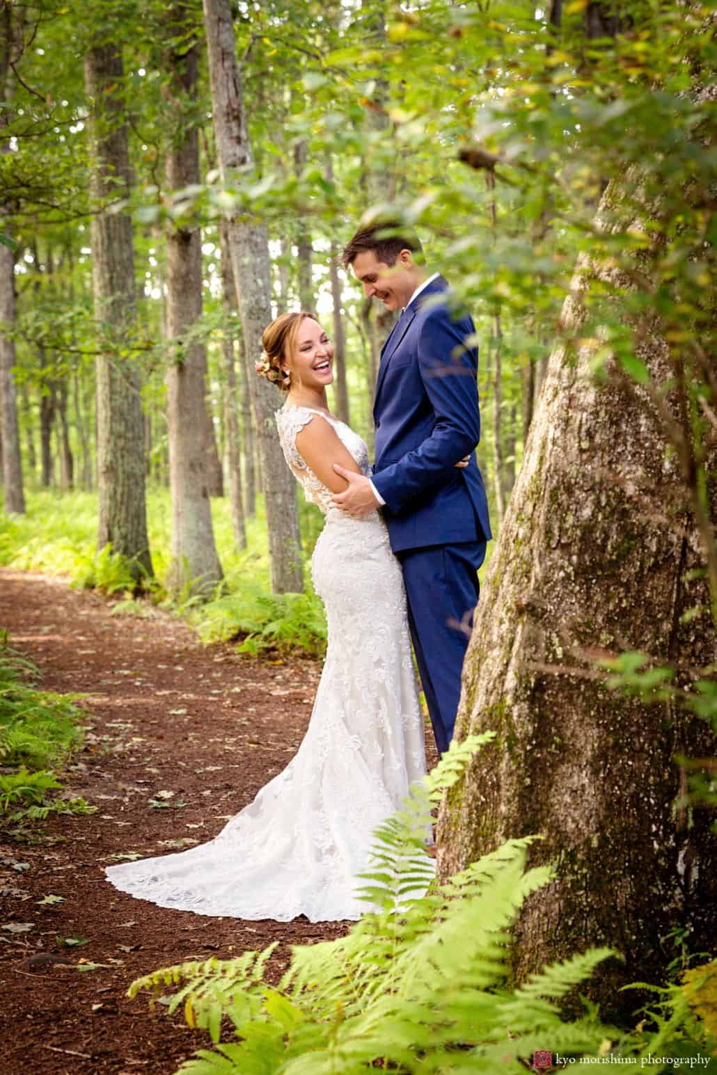 Bride and groom smile on mulched path in wooded area at Woodloch Pines resort, Castle Couture bridal gown, dark blue groom's suit, outdoor wedding photographer.