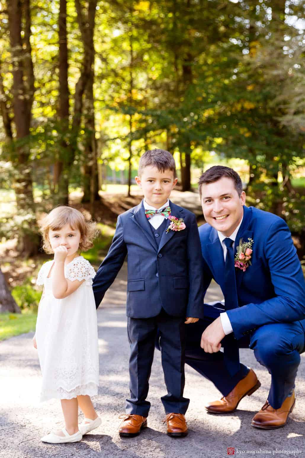 Groom poses with ring bearer and flower girl along wooded path in Woodloch Pines, cute wedding pictures, ourtood wedding photography ideas, Poconos wedding photographer. Woodloch Pines wedding.