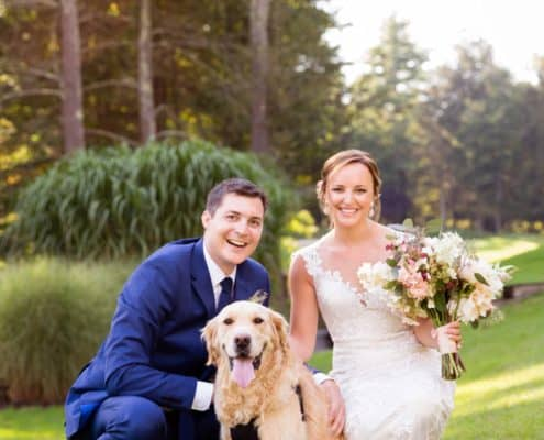 Bride and groom pose outside with their golden retriever at Woodloch Pines resort, white and pale peach bouquet with burgundy accents by Fox Hill Farm Experience, Castle Couture wedding gown, cobalt blue groom's suit, outdoor poconos wedding photographer., Woodloch Pines wedding, cute wedding pictures