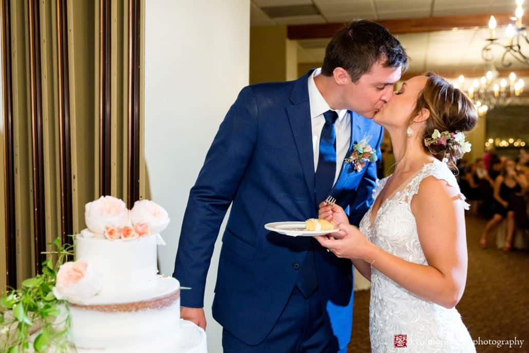 Bride and groom kiss next to wedding cake while bride holds plate with slice of cake, Castle Couture wedding gown, cobalt blue groom's suit, Fox Hill Farm Experience boutineer and bridal hair flowers, burgundy and white flowers with eucalyptus, naked wedding cake with peonies, Woodloch Pines reception, Poconos resort wedding photographer.