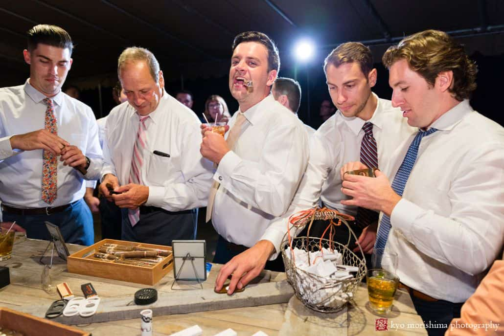 Groomsmen gather at table with cigars and drinks at Woodloch Pines resort, Poconos Summer wedding photographer.