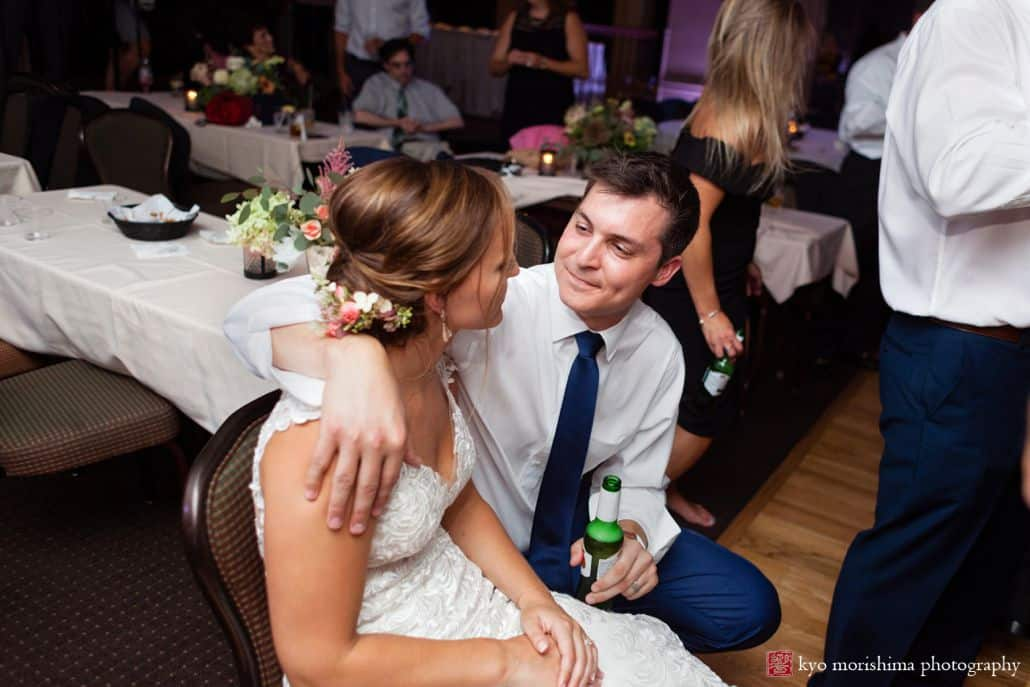 Bride and groom sit together and look at one another towards end of reception at Woodloch Pines in Poconos, Castle Couture bridal gown, Poconos wedding photographer.