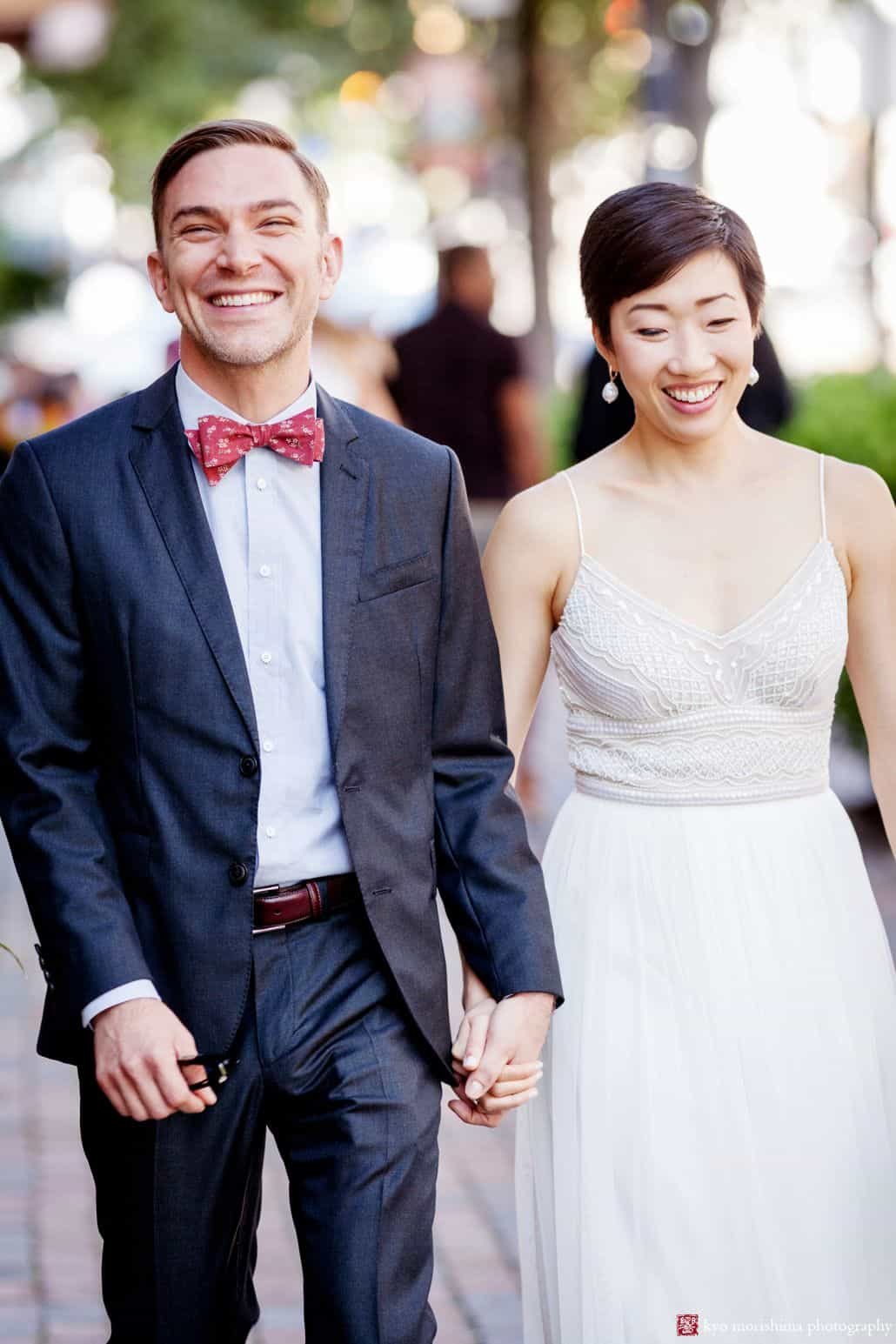 Candid wedding portrait of bicultural couple walking down city street on September wedding day; groom wears red bow tie