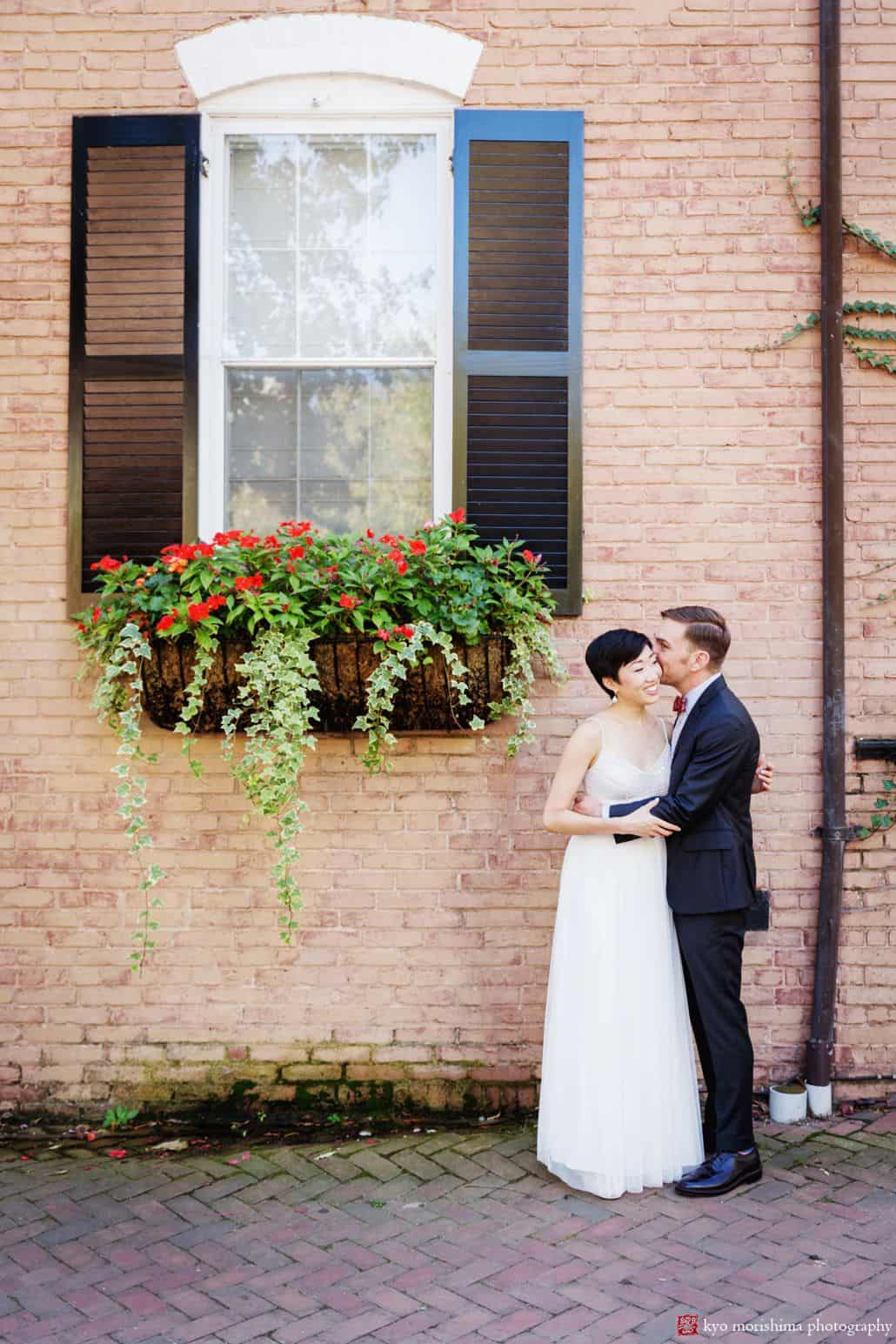 Bride and groom portrait against brick wall in Old Town Alexandria before their ceremony at small unique wedding venue Carlyle House in Old Town Alexandria