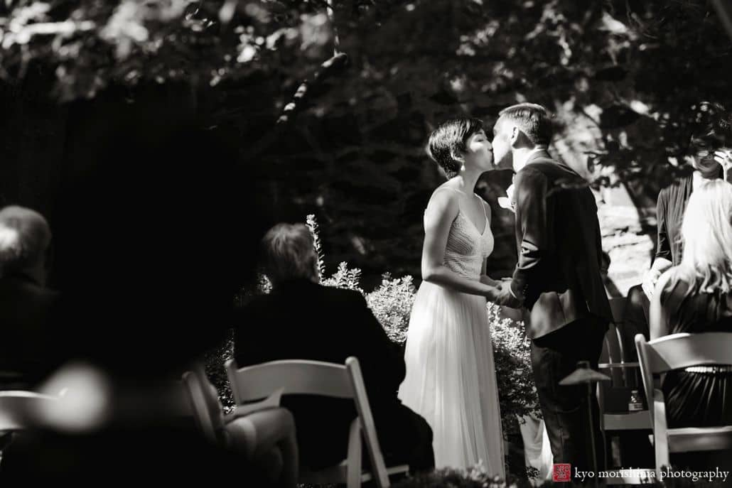 Bride and groom kiss during high noon ceremony at unique small wedding venue Carlyle House in Old Town Alexandria.