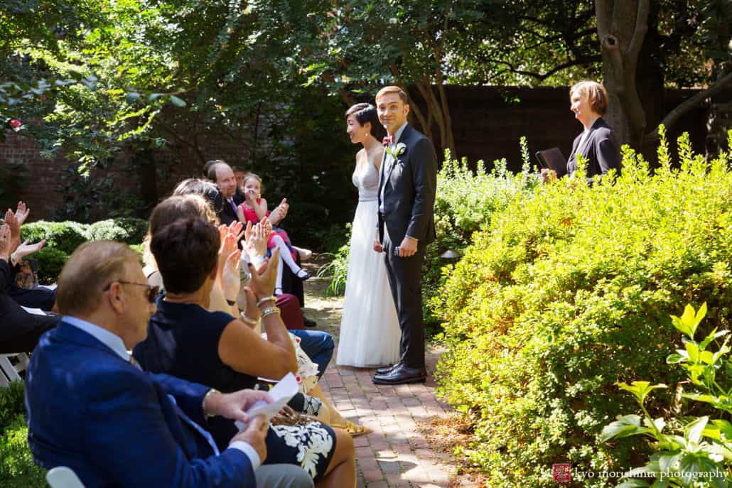 Groom glances at camera as couple exits their ceremony, by candid DC wedding photographer Kyo Morishima