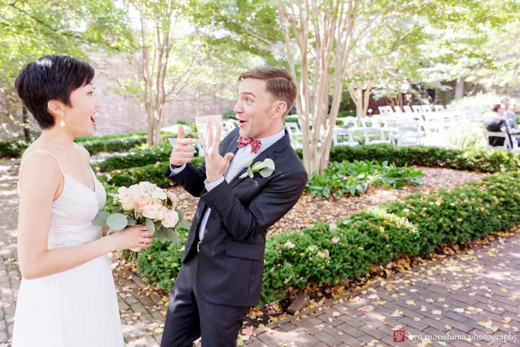 Fun wedding photo as groom shows bride how crazy it is that he's wearing a wedding ring nowFun wedding photo as groom shows bride how crazy it is that he's wearing a wedding ring now