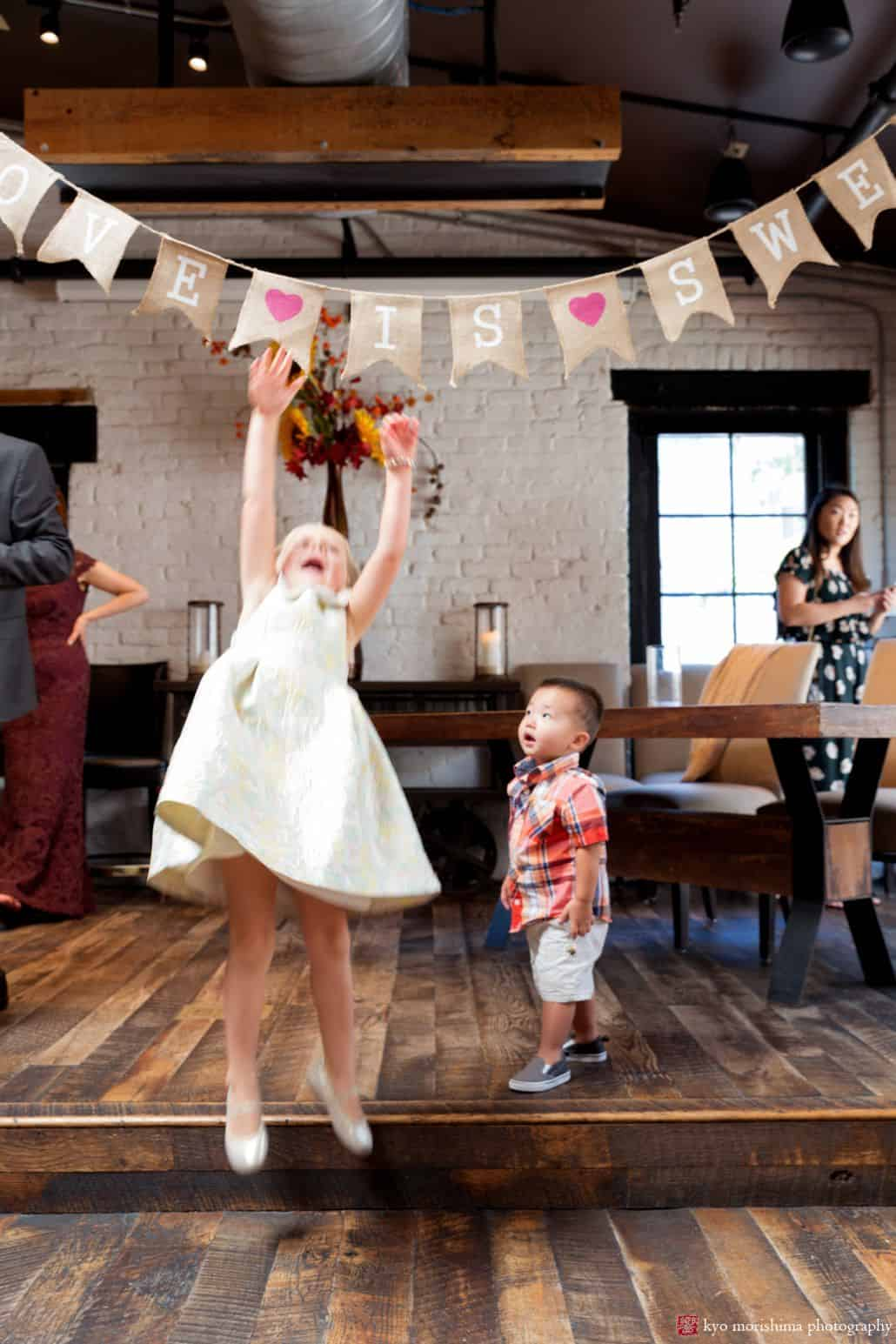 Two young guests jump up to play with flag garland at Virtue Feed and Grain wedding in Old Town Alexandria