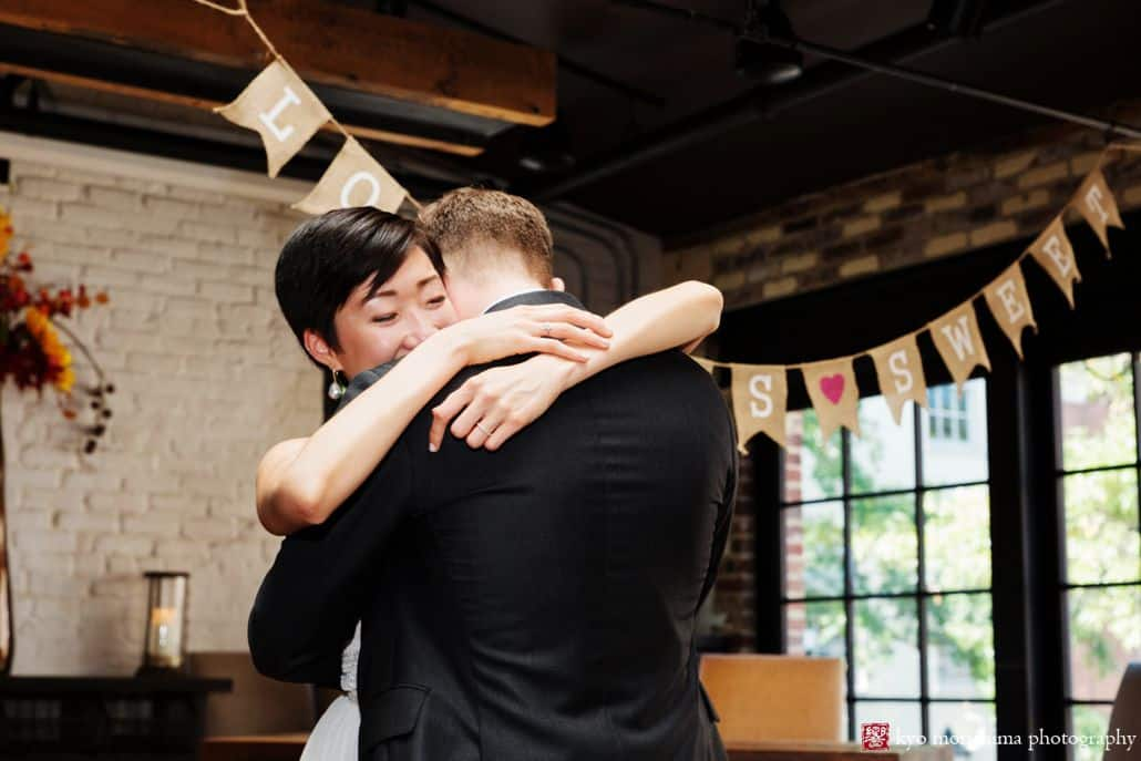 Bride and groom have an emotional embrace during first dance at Virtue Feed and Grain wedding, by photojournalistic wedding photographer Kyo Morishima