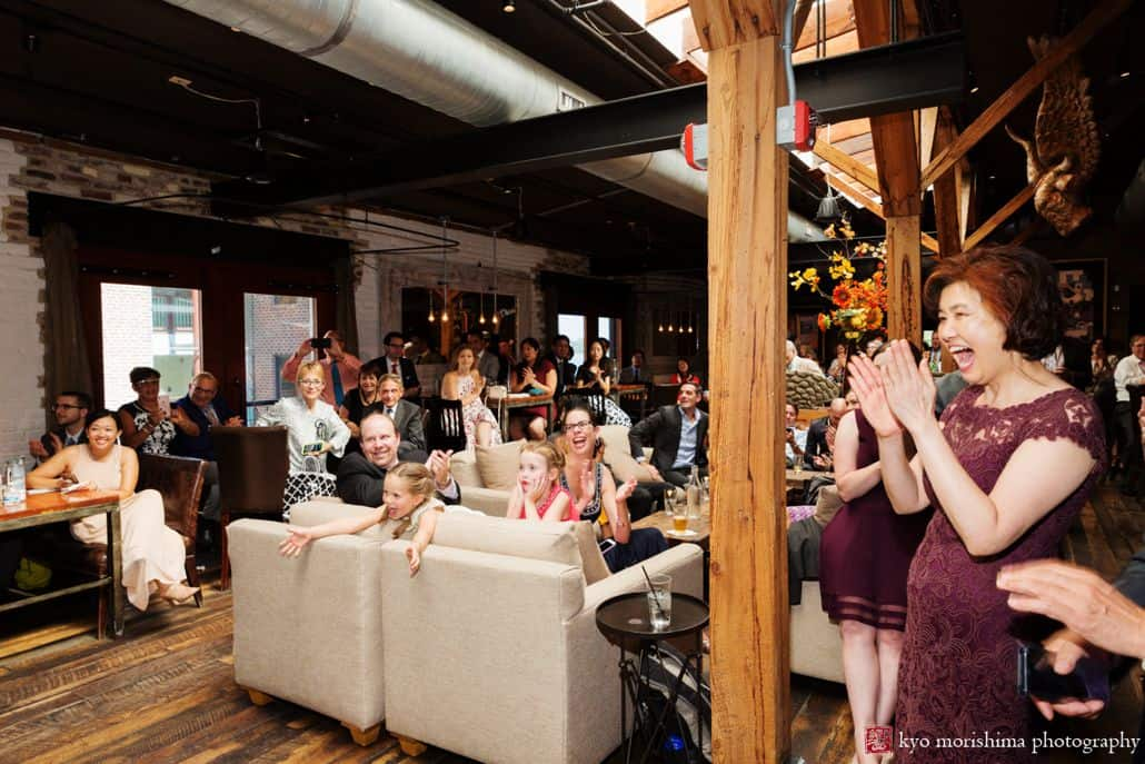 Guests react enthusiastically to first dance at Virtue Feed and Grain wedding; candid moment by DC photographer Kyo morishima