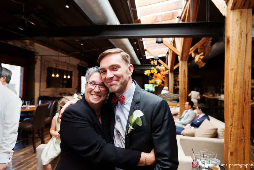 Groom and guest hug and smile for the camera at Virtue Feed and Grain wedding by candid photographer Kyo Morishima