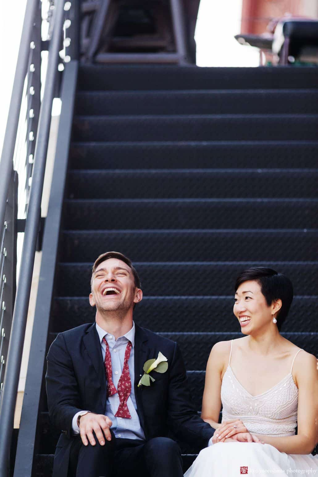Fun wedding photo of bride and groom sitting on fire escape steps outside Virtue Feed and Grain in Old Town Alexandria
