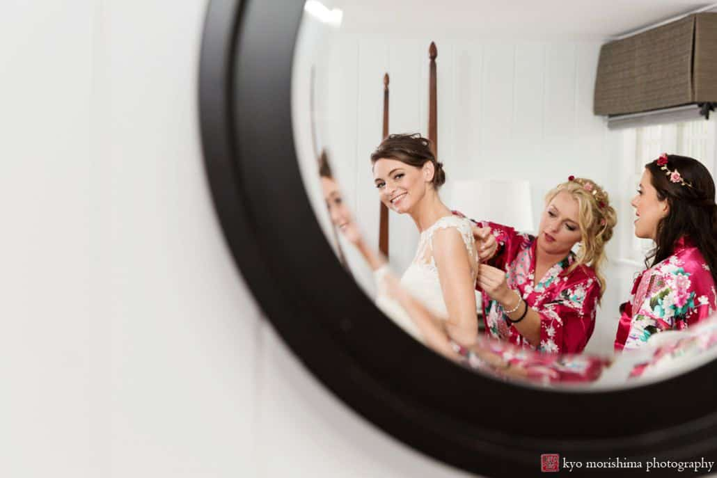 Bride smiles into mirror as she gets dressed at Chauncey Hotel and Laurie House Garden Pavilion wedding