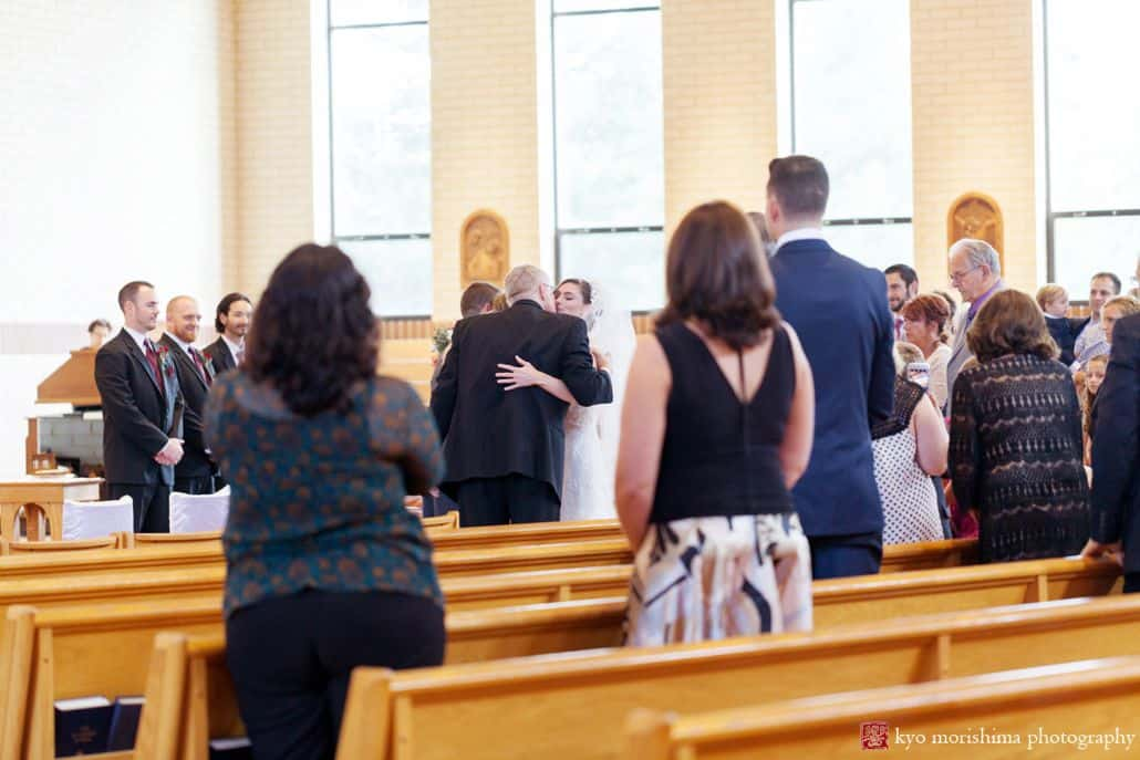 Bride hugs parents during St. Magdalen Church wedding in Flemington, NJ