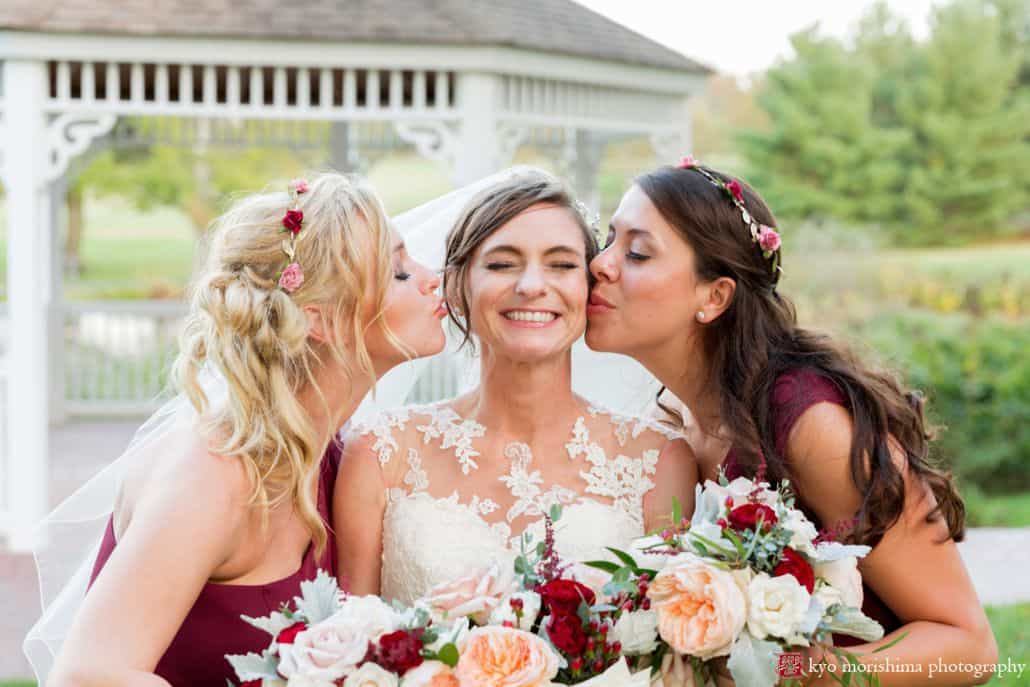 Wedding poses examples: bridesmaids kiss bride in front of gazebo at Chauncey Hotel and Laurie House Garden Pavilion wedding, Princeton, NJ
