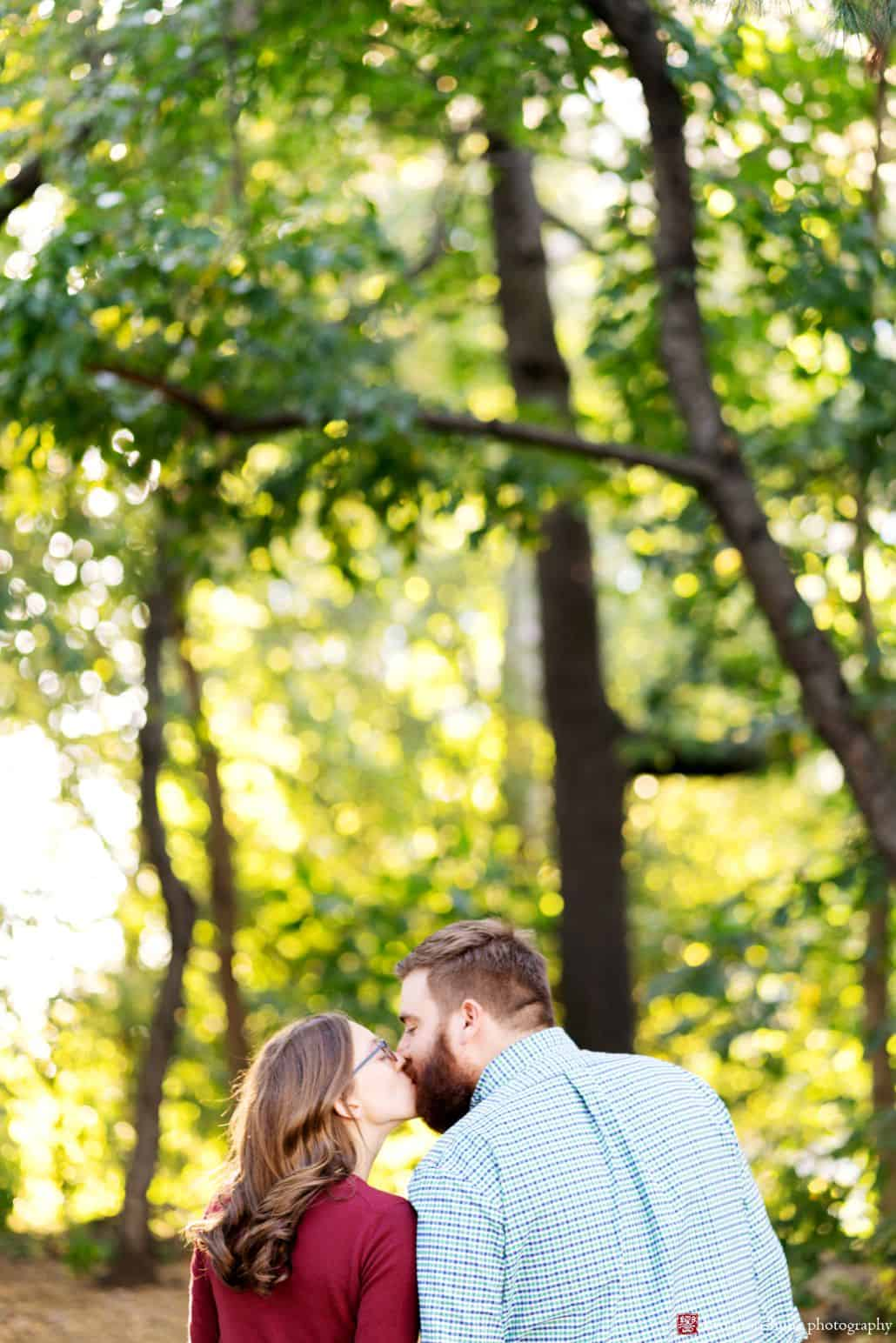 Couple kisses in Prospect Park with bright sunlight filtering through the leaves