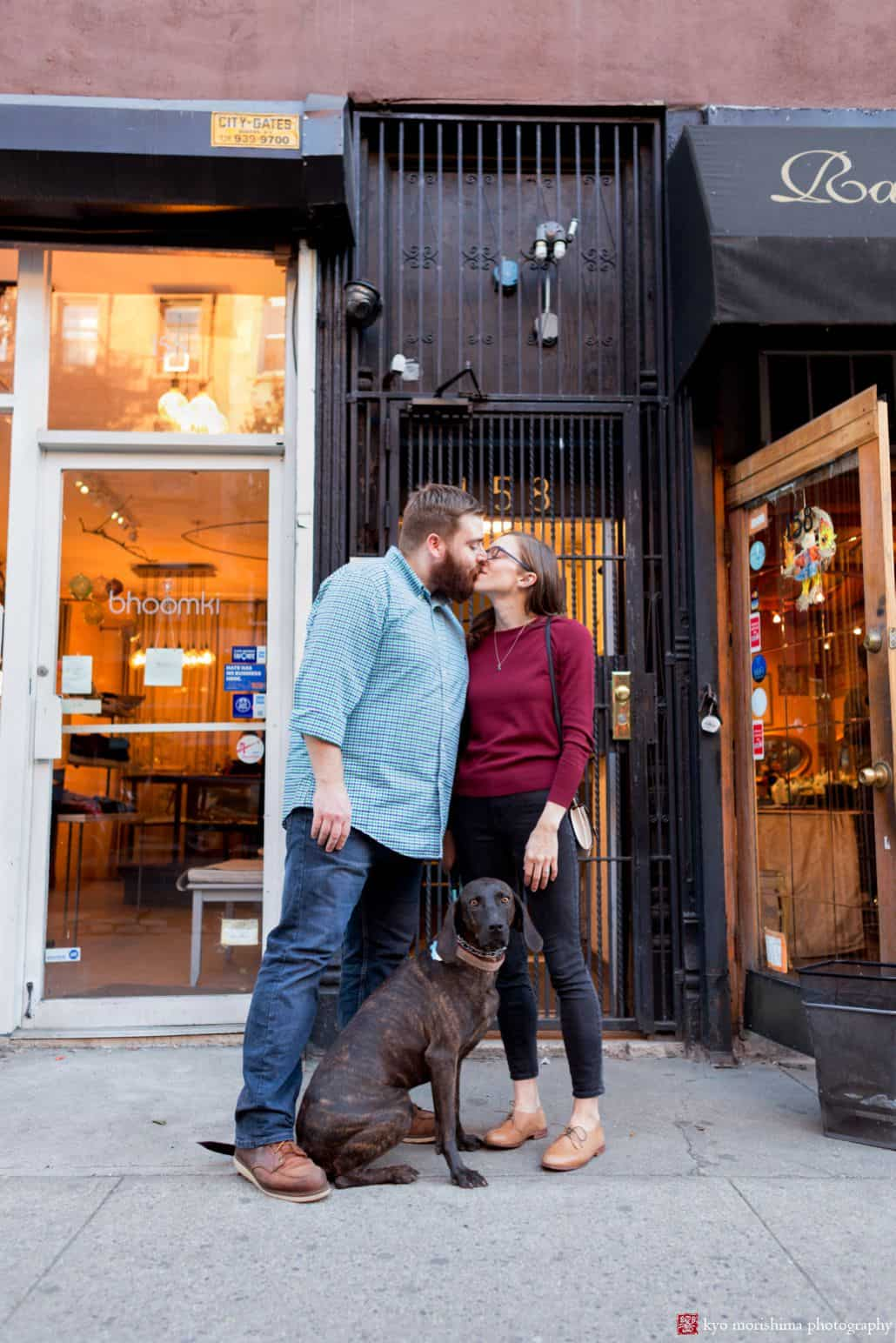Couple kisses in Brooklyn storefront while holding their Weimaraner dog's leash, by Park Slope photographer Kyo Morishima