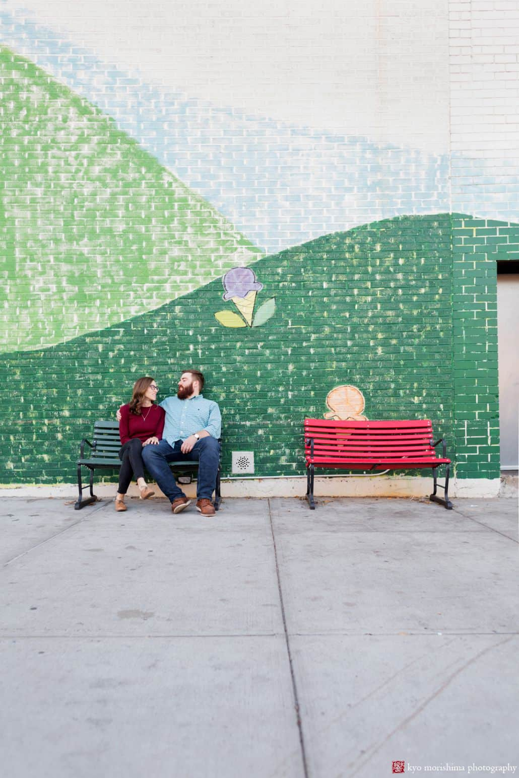 Park Slope engagement photo: couple sits on park bench in front of painted mural
