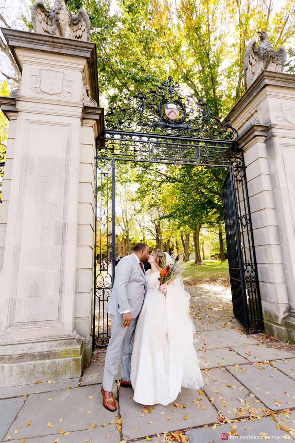 First wedding day kiss in front of Nassau Hall gates at Princeton University; fall wedding