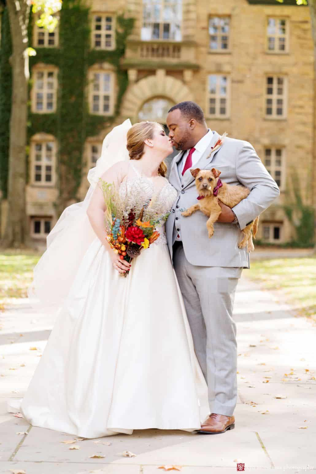 Fall wedding portrait at Princeton University with groom holding small dog; wedding bouquet with fall colors