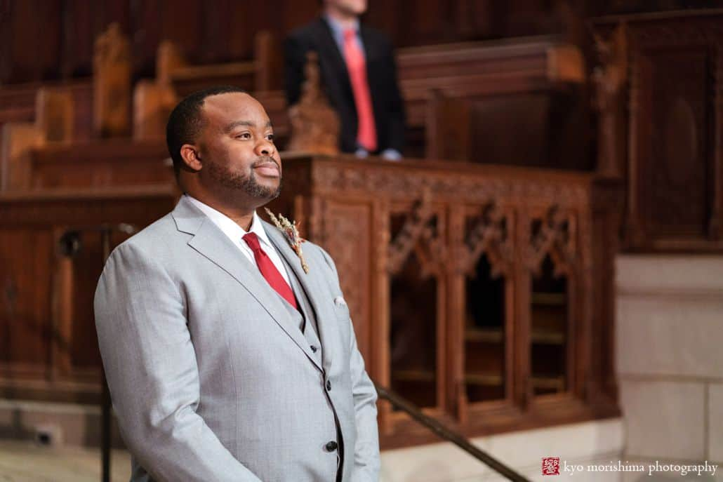 Groom awaits bride at Princeton University chapel wedding, wearing light grey suit with red tie
