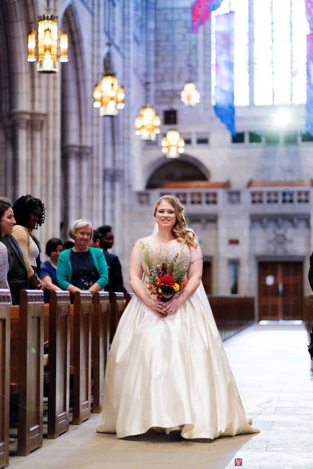 Bride walks down the aisle at Princeton University chapel wearing dress by Christina Wu with fall themed wedding bouquet