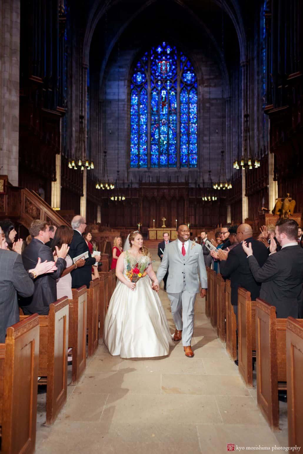Bride and groom depart Princeton University chapel wedding, holding hands