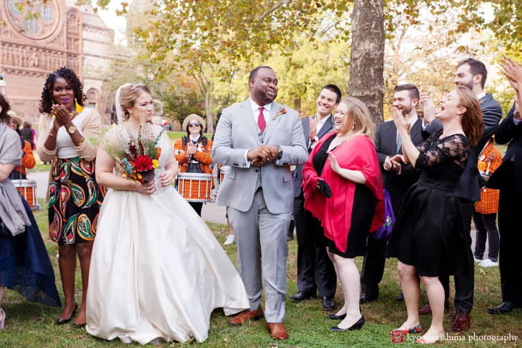 Bride and groom laugh with guests on Princeton University quad after October ceremony