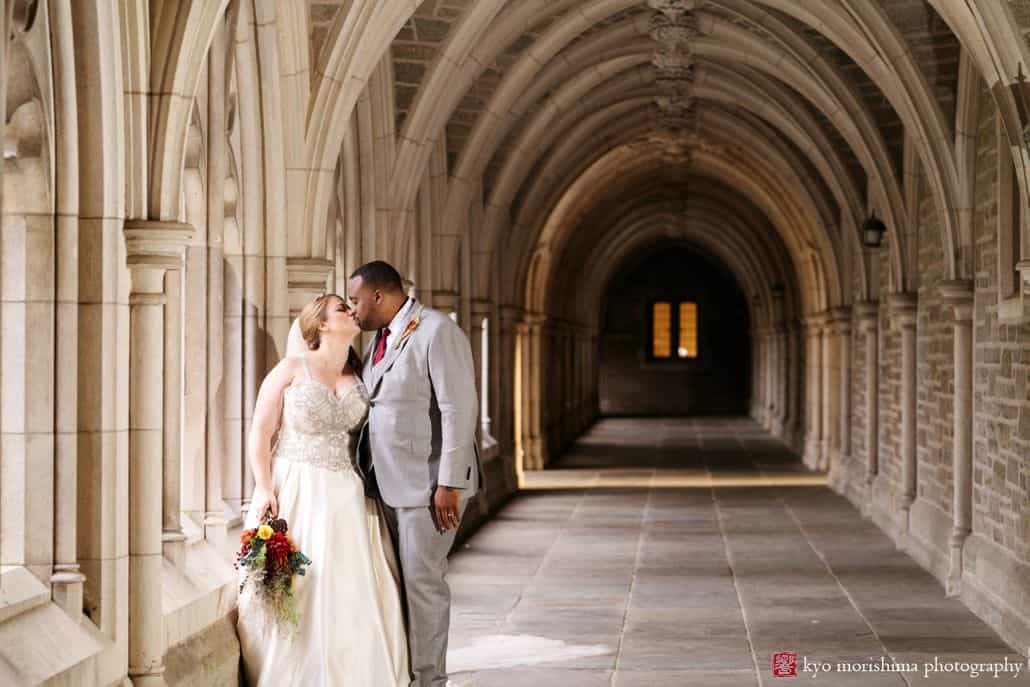 Bride and groom kiss in stone colonnade at Princeton University wedding
