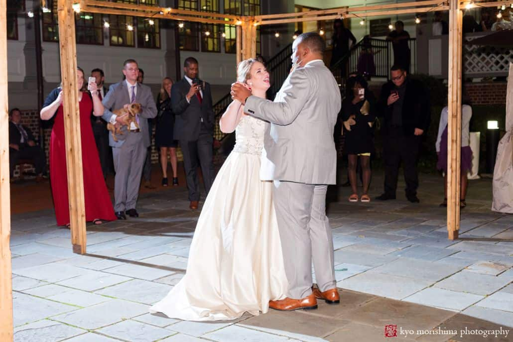 Bride and groom dance on stone pavilion with bulb string lights during October wedding at Princeton University Cap and Gown club