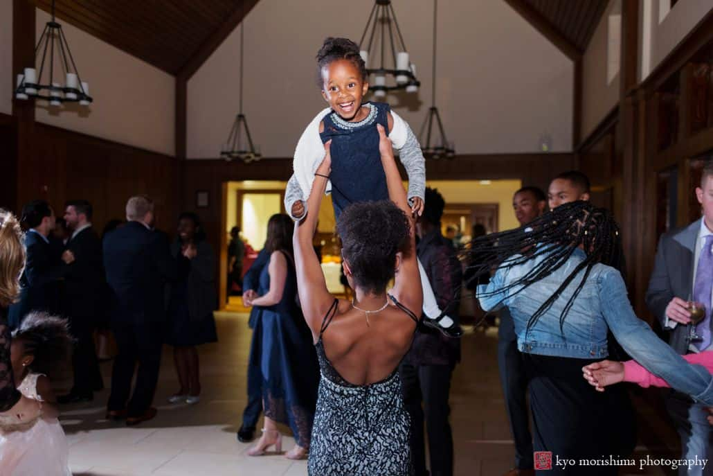 Wedding guest lifts child into the air during dancing at Princeton University Cap and Gown Club