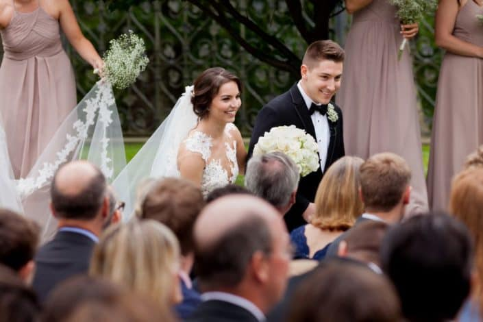 Bride and groom, seen over the tops of their guests' heads, depart the wedding ceremony at Jasna Polana. Bride wears Pronovias. Flowers by Janet Makrancy.