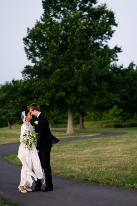 Bride and groom kiss on a path outside Mercer Oaks Country Club with thunderstorm approaching. West Windsor Township, NJ.