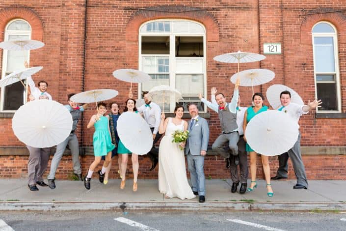 Fun wedding party portrait ideas: jumping with parasols at Brooklyn Navy Yard