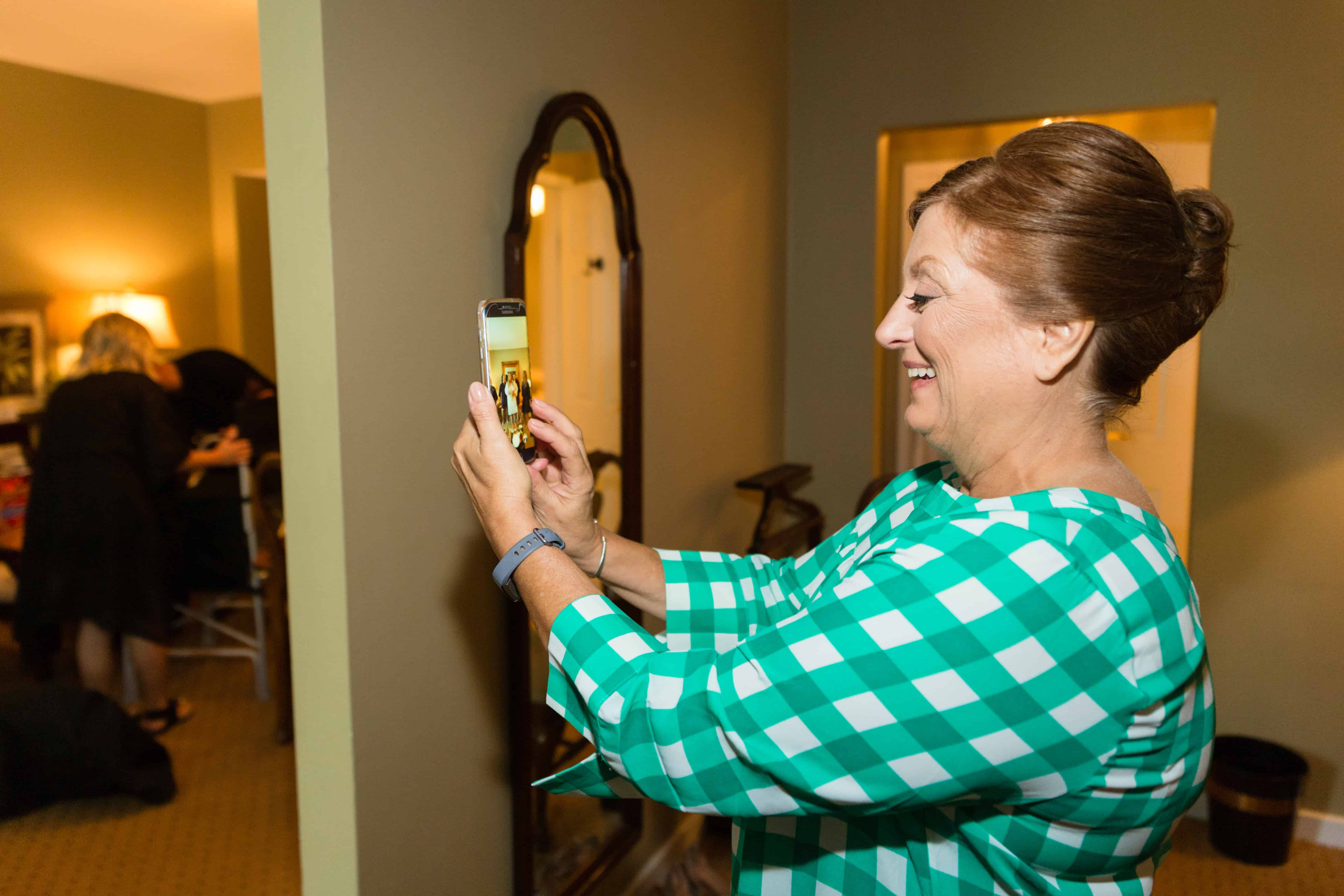 Mother of the bride takes an iphone photo while getting ready before Nassau Inn Princeton wedding