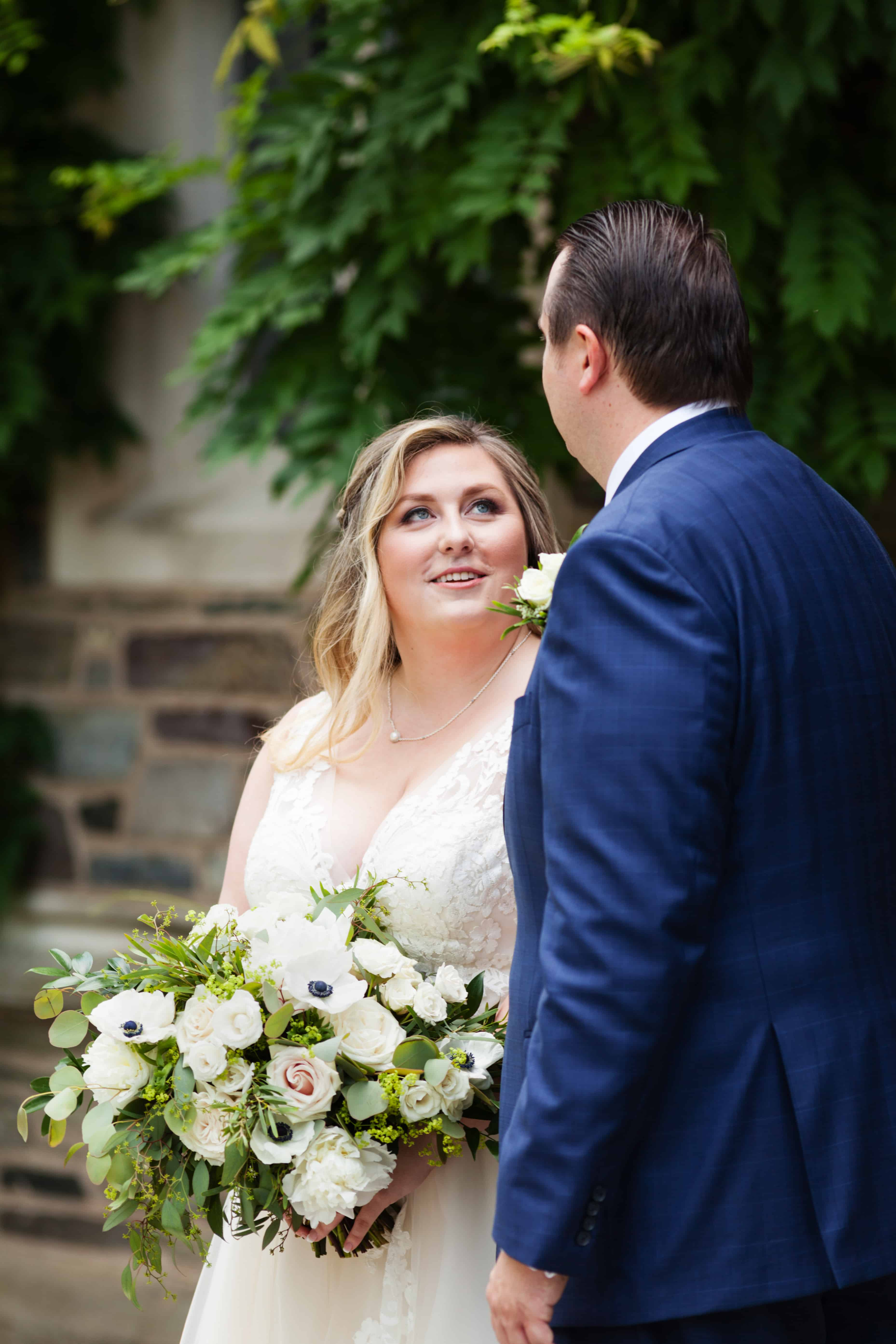 Bride looks up at groom, holding Petal Pushers bouquet, during Princeton University campus wedding portrait session