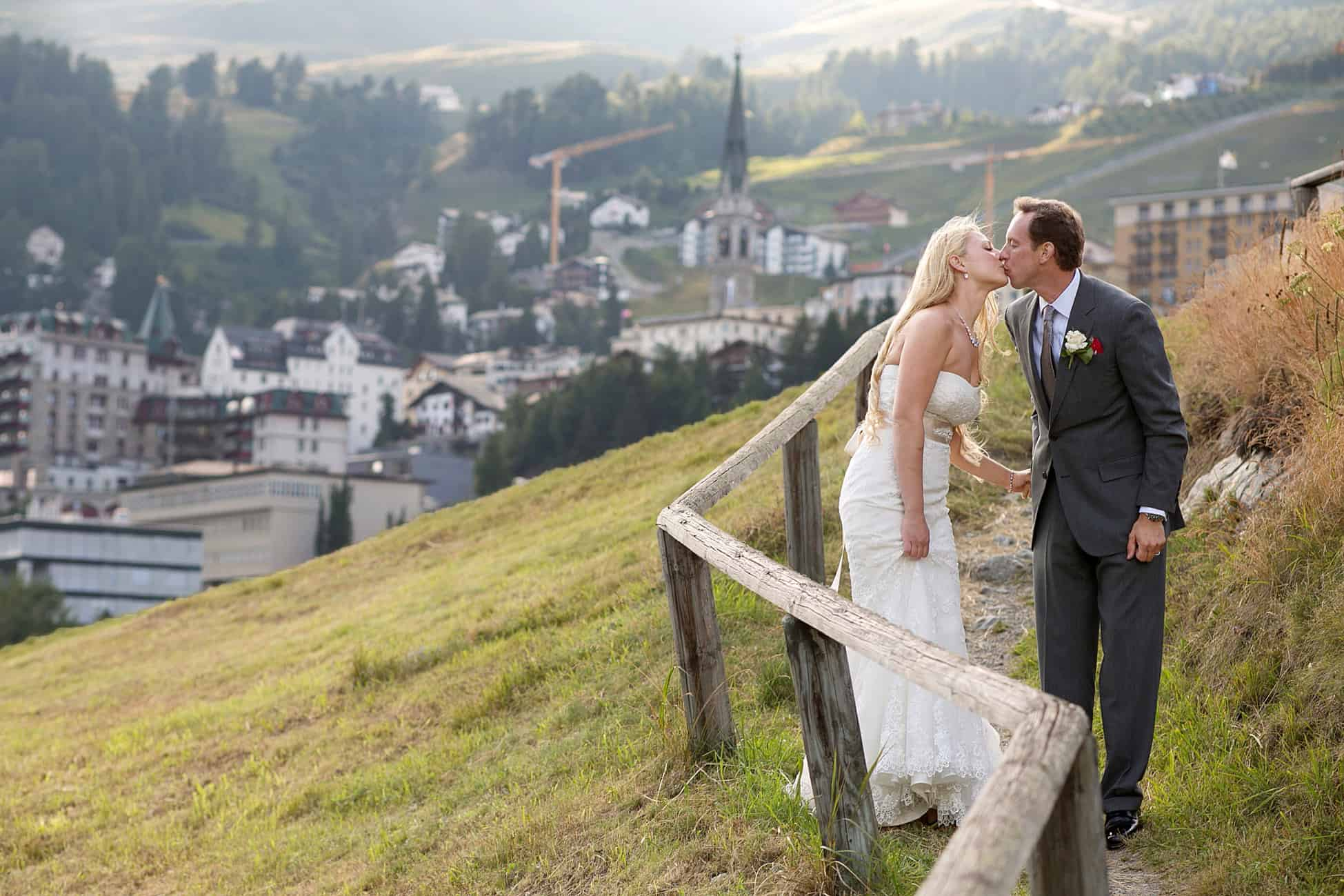 Couple kiss as they walk down gravel path near St. Moritz in the Swiss Alps, photographed by destination wedding photographer in Europe.