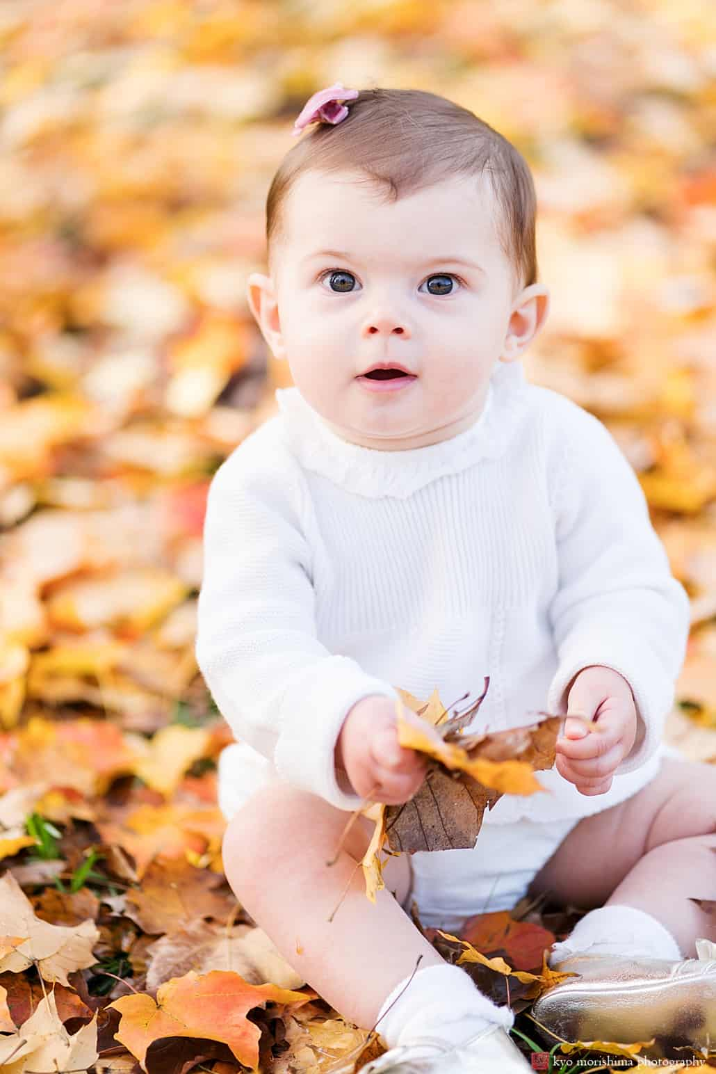 Princeton baby photographer adorable baby girl wearing white sits outside amidst golden fall leaves