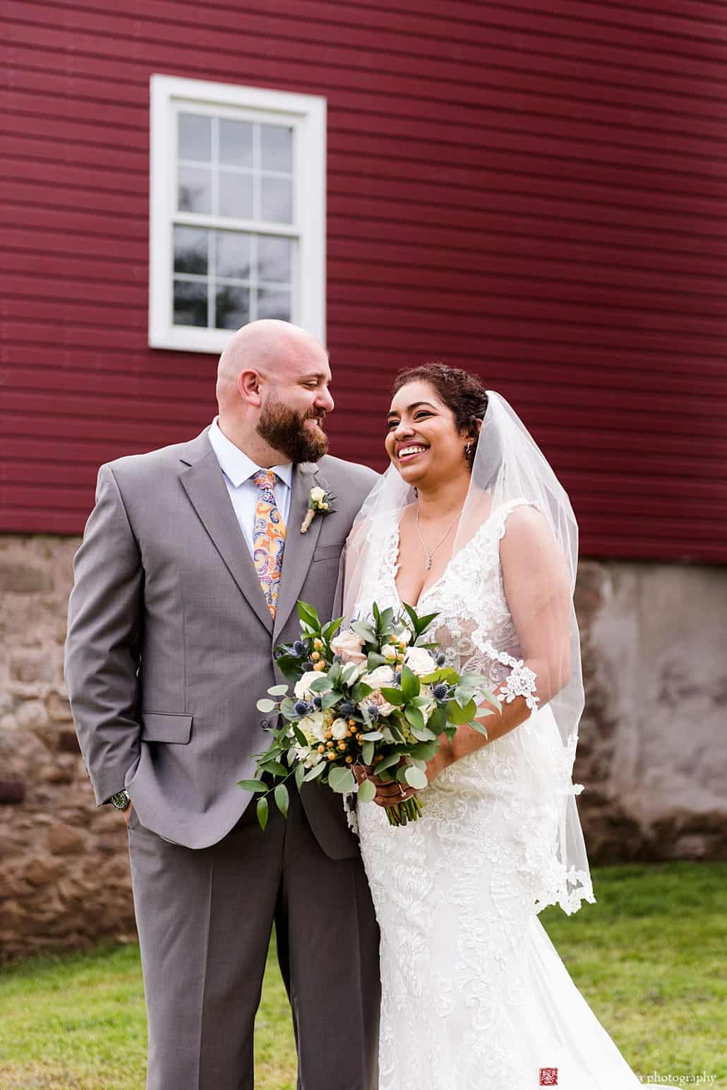 Candid wedding photographer NJ: relaxed portrait in front of the red barn at Glenmoore Farm in Hopewell NJ