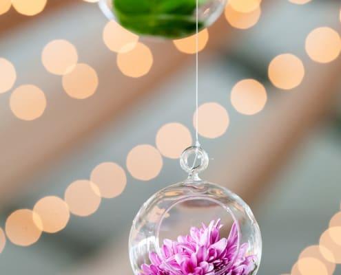 Lush purple flower inside a hanging glass globe: easy and creative wedding decor idea